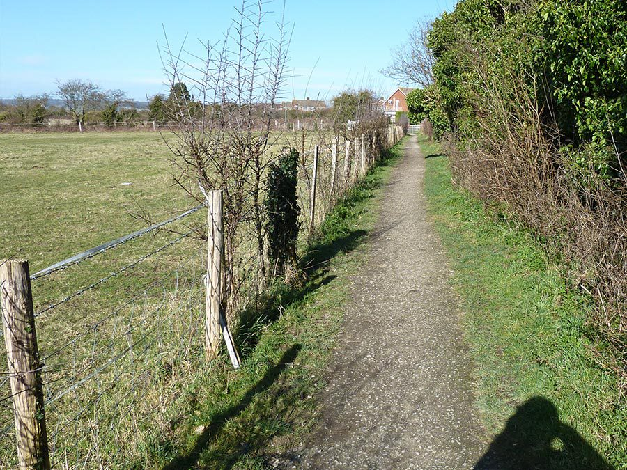 A narrow and uneven country footpath, bordered by a wonky fence.